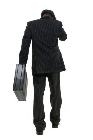 핀 스트라이프 슈트 & 앰프, 모자에서 매력적인 비즈니스 사람. 몸 전체 카메라에서 멀리 서류 가방으로 걷고 쐈 어.