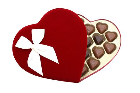 Deep red velvet heart shaped box with heart shaped dark and light chocolate truffles isolated on white