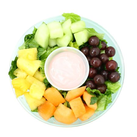 Small fruit tray with cantaloupe, honeydew, pineapple, grapes and strawberry yogurt. photo