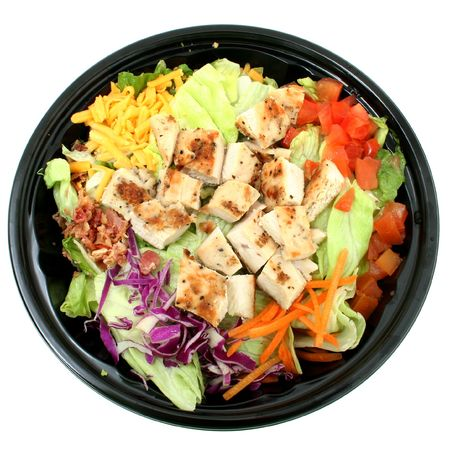 Fast food salad with grilled chicken, lettuce, tomato, cheese.