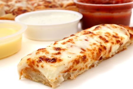 Take cheese pizza sticks with a container of marinara sauce, ranch dressing and garlic butter.  Focus on pizza stick in front.  Stock Photo