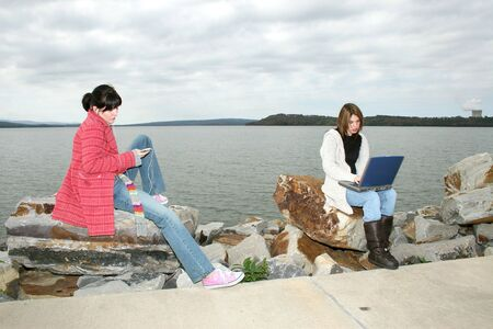 american downloads: Two beautiful young woman (hispanic and caucasian) sitting outside by the fireplace with laptop.  Wearing winter clothes.
