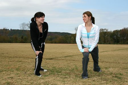 Two friends stretching at the track.  Shot outdoors. Imagens