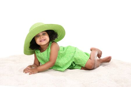 Beautiful Young Girl Laying In the Sand in green summer clothes and big green hat.  Beautiful eyes. Stock Photo - 4072143