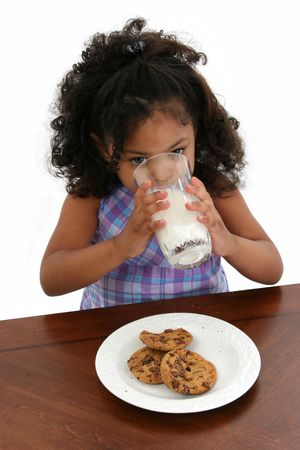 Three-year-old girl drinking milk and eating cookies. Standard-Bild