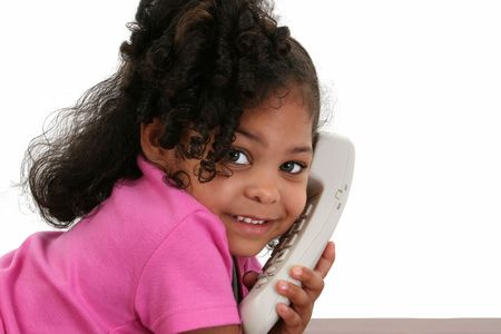 Beautiful three-year-old African American girl talking on phone.  photo