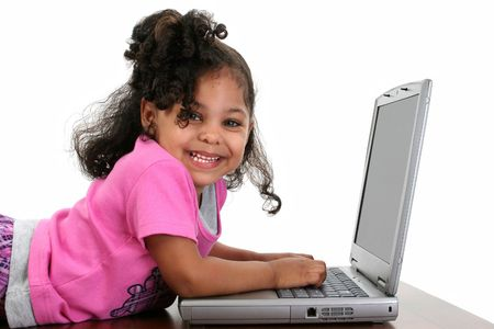 Three-year-old toddler girl in pink playing with a laptop computer.
