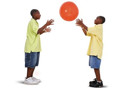 Two brother tossing giant orange ball back and forth. Shot in studio over white with the Canon 20D. Stock Photo