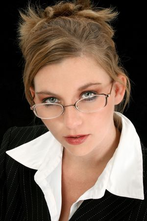 Beautiful 25 year old woman in suit over black. Wearing eyeglasses. photo