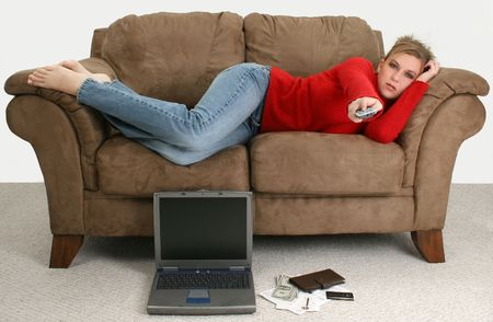 Beautiful young woman taking a break from balancing her bills online.  Laptop, cash, credit card, bills and checkbook on the floor in front of her as she relaxes on the couch watching tv. photo