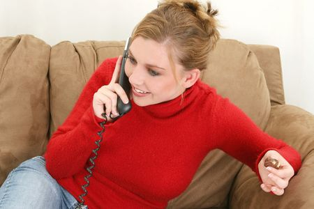 Beautiful twenty-something woman in red sweater sitting on couch eating chocolate and talking on phone. photo