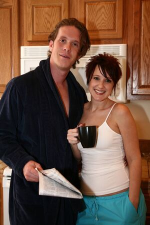 house robes: Attractive 30 something couple at him in kitchen. Stock Photo