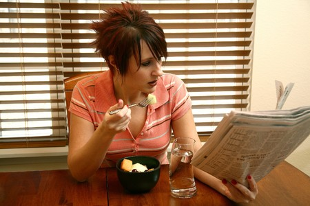 30 something: Beautiful 30 something woman eating fresh fruit and reading newspaper.