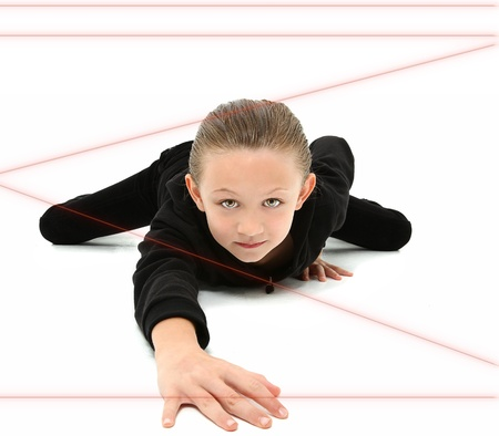 Adorable 7 year old girl dressed as spy crawling through red laser beams over white background.