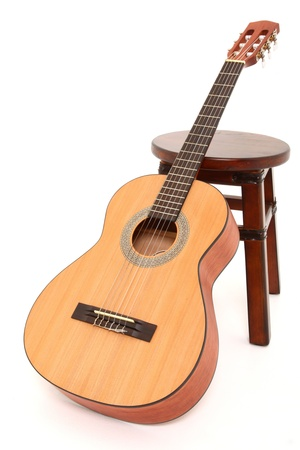 stool: Child size acoustic guitar leaning against a wooden stool over white background.