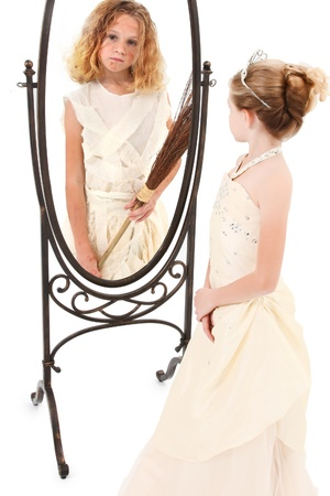 Beautiful 7 year old girl playint the part of peasant and princess in mirror over white background.  Theatre concept.