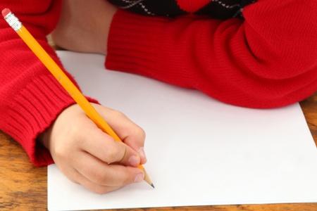 old year: Attraente 7 anni francese americano ragazzo nella scuola scrivania su bianco scrittura su carta.