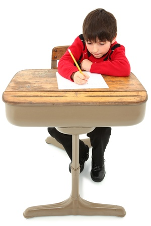 Attractive 7 year old french american boy in school desk over white writting on paper. photo