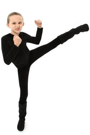 7 year old girl: Adorable 7 year old girl in black demonstrating a martial arts kick over white background.