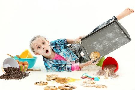 clumsy: Adorabile ragazza 7 anni cottura i cookie che cade il pasticcio rendendo su sfondo bianco. Archivio Fotografico