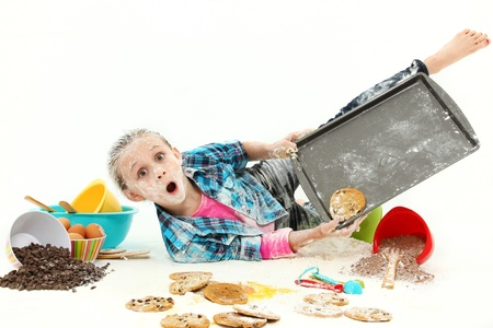 Adorable 7 year old girl baking cookies falling making mess over white background.
