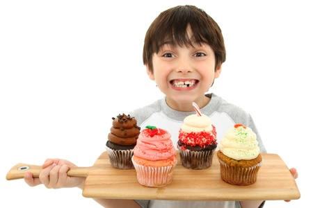 Adorable 7 year old boy smiling with tray of cupcakes.  Strawberry, chocolate, carrot cake, pepperment. Reklamní fotografie