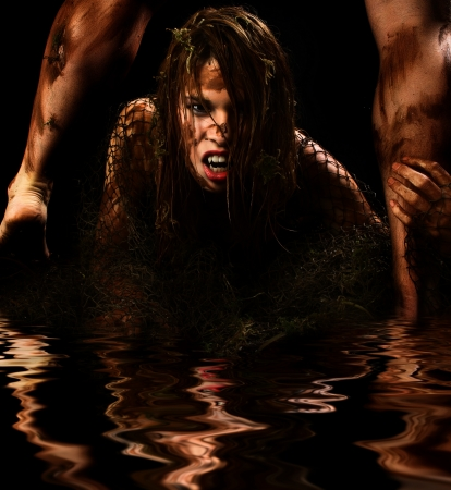female vampire: Fantasy monster portrait of couple covered in mud in water.
