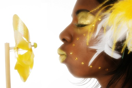 Beautiful young african american woman in yellow feathers, beads and glitter over white background.