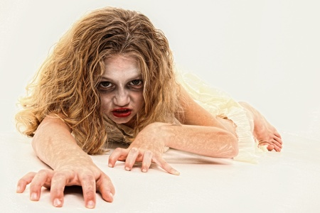7 year old girl: Adorable 7 year old girl in Zombie costume over white background. Stock Photo