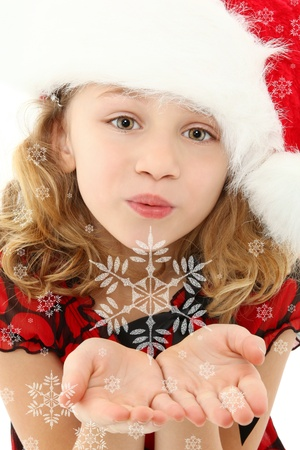 seven year old: Beautiful seven year old girl in santa hat blowing snowflakes to camera.