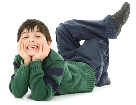 Adorable and very flexible 7 year old french american boy laying on belly with legs twisted behind him.  Smiling. Stock Photo