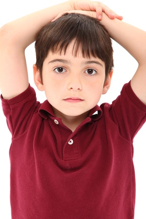 Attractive eight year old french american boy with serious expression, hands on head, casual shirt over white background. photo