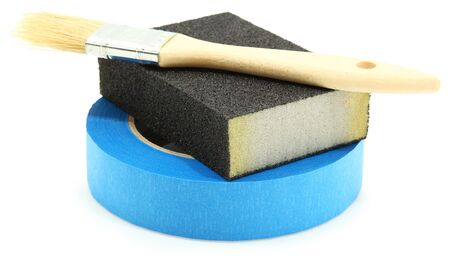 Painters tape, sanding block and paint brush stacked over white background. Stock Photo