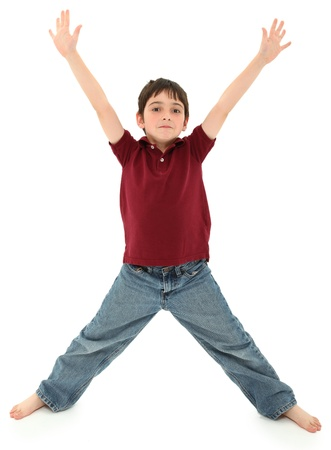Attractive 8 year old french american boy standing in the shape of a letter x or ready to hug.  Standing over white background. photo