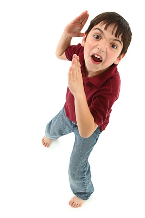 Adorable 8 year old french american boy making silly karate faces and poses over white background. Stock Photo