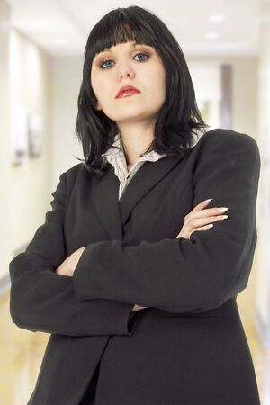 Attractive 19 year old woman in suit with seriuos expression and arms crossed. In office or school hallway. photo
