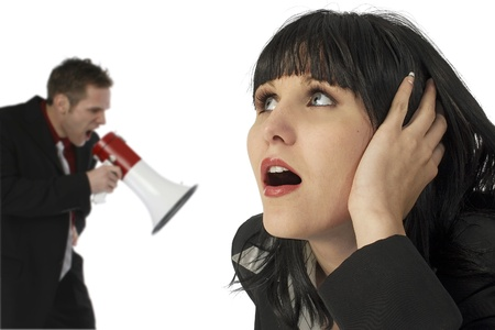 bawl: Attractive young woman covering ears while angry man yells in electric bullhorn over white. Stock Photo