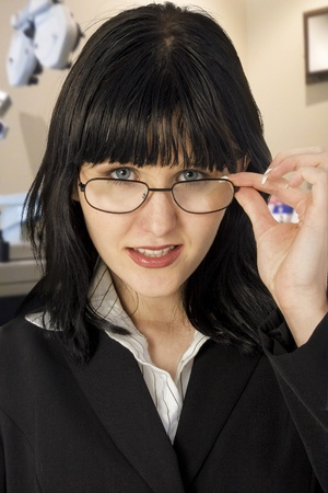 Attractive young woman in glasses in eye examination room. photo