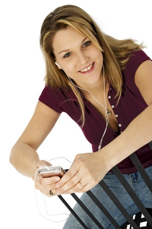 Attractive happy 25 year old woman listening to digital audio device photo