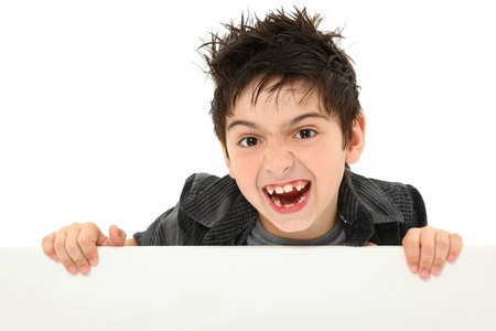 animal teeth: Adorable and funny 8 year old boy making silly animal face while holding blank canvas over white.