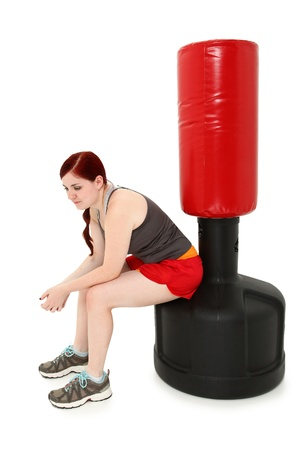 Attractive 19 year old woman sitting resting on free standing heavy bag after workout. photo