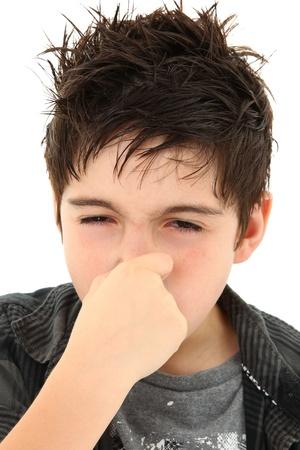 Adorable niño hacer expresión maloliente cara de alergia en blanco.