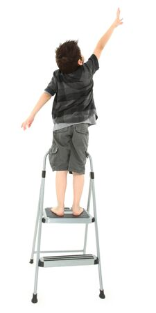 Young boy on step ladder reaching up over white background.