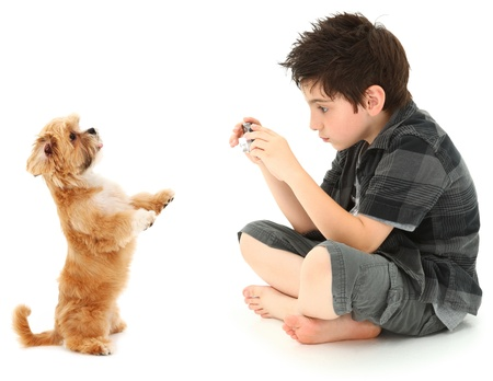 Adorable 8 year old boy shooting photos of his dog with digital camera over white background.