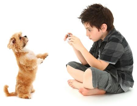 point and shoot: Ni�o de 8 a�os adorable tiro fotos de su perro con c�mara digital sobre fondo blanco. Foto de archivo