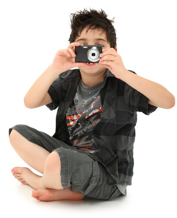 Attractive 8 year old boy aiming digital camera towards camera sitting over white background. photo