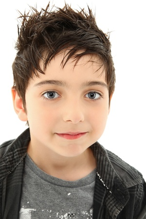 Close up young boy slight smile, hazel eyes, spiky, brown hair over white.