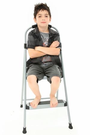 魅力的な 8 年の古い男の子腕を白い背景の上のステップはしごを組んで座っています。
