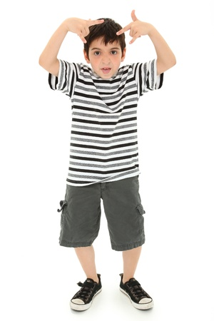 Adorable 8 year old boy making silly faces and gestures over white background.