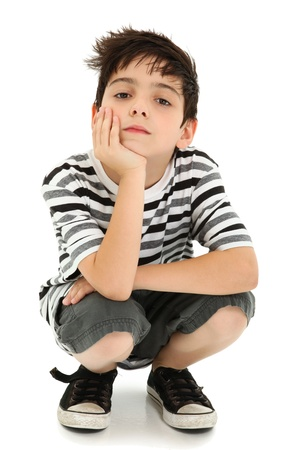 squatting: Boy with chin resting on hand with watching expression over white. Stock Photo
